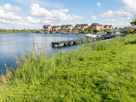 waterside: ALMERE, NETHERLANDS - AUG 24, 2014: Waterside houses in green residential suburb, Almere in the province of Flevoland near Amsterdam Editorial