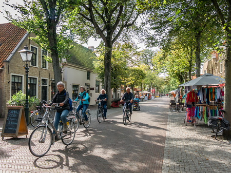 VLIELAND, NETHERLANDS - SEP 22, 2014: Tourists sightseeing on bicycles in Main Street of East-Vlieland on Vlieland island in the Waddensea, Netherlands