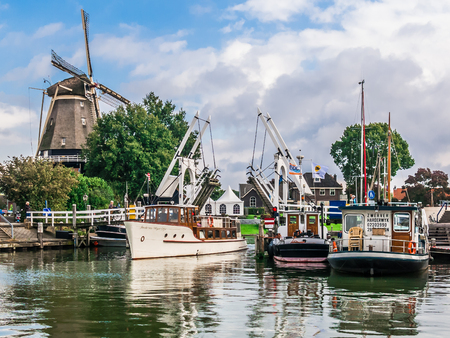 HARDERWIJK, NETHERLANDS - SEPT 26, 2014: Windmill, bridge and boats in the harbour of Harderwijk, Netherlands 報道画像