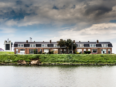 ijmuiden: VELSEN, NETHERLANDS - MAY 8, 2015: Row of waterfront terraced working-class houses in the industrial area of IJmuiden and Velsen in the Netherlands