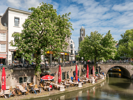 UTRECHT, NETHERLANDS - MAY 21, 2015: Dom Tower and people on outdoor terrace of restaurant alongside Oudegracht canal in the city of Utrecht, Netherlands