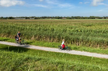 bicycling: Family recreational bicycling in the fields on vacation on the island Schiermonnikoog, Netherlands Editorial