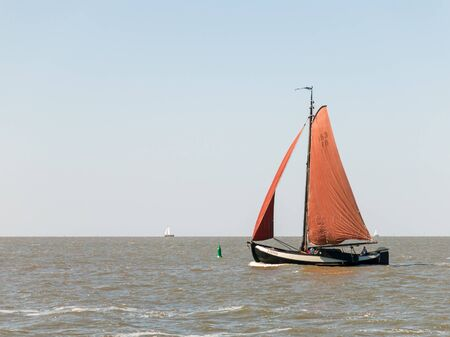 wadden: Classic Dutch sailboat sailing on the Wadden Sea in the Netherlands