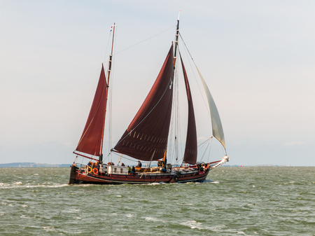 wadden: Classic Dutch sailboat of the brown fleet sailing on the Wadden Sea in the Netherlands Editorial