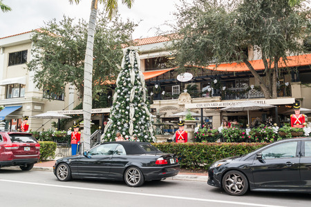 streetscene: NAPLES, USA - DEC 10, 2015: Streetscene with shops, restaurants, cars and christmas tree on 13th Avenue South in the city of Naples, Collier county, Florida, USA
