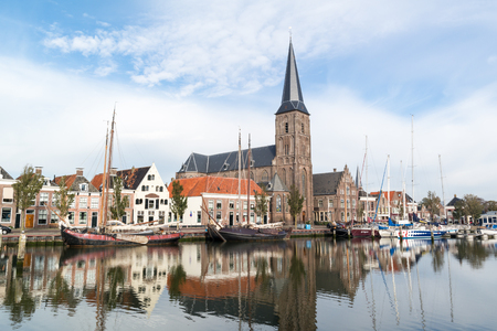 gables: Saint Michaels Church and historic houses on quay of Zuiderhaven harbour canal with boats in Harlingen, Friesland, Netherlands Editorial