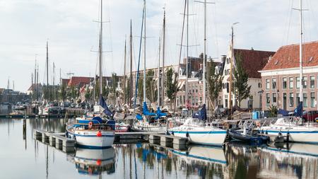 literas: Zuiderhaven del puerto del canal con los barcos y casas antiguas en muelle en Harlingen, Frisia, Países Bajos