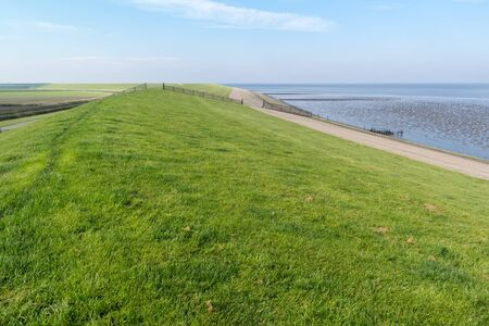 Sea dyke between Frisian polders and Wadden Sea - coastline of Friesland, Netherlands Stock Photo