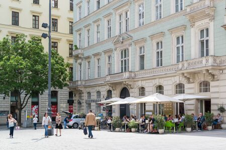 streetscene: Street scene of Freyung with outdoor cafe terrace and people in old city centre of Vienna, Austria