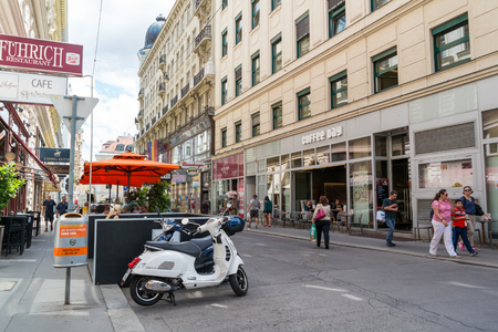 inner city: Street scene of Tegetthoffstrasse with people, coffee house, scooter and outdoor cafe in inner city of Vienna, Austria