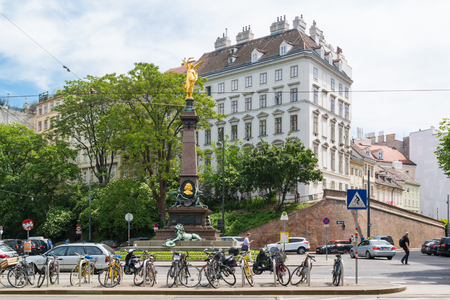 Street scene with Liebenberg monument, bicycles, people and traffic on Ringstrasse in inner city of Vienna, Austria