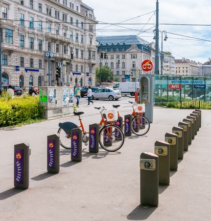 streetscene: Schottenring Ringstrasse near Sigmund Freud Park with citybike station, people and traffic in Vienna, Austria
