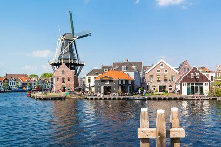 Waterfront cafe met mensen, windmolen Adriaan en Spaarne rivier in Haarlem, Holland, Nederland