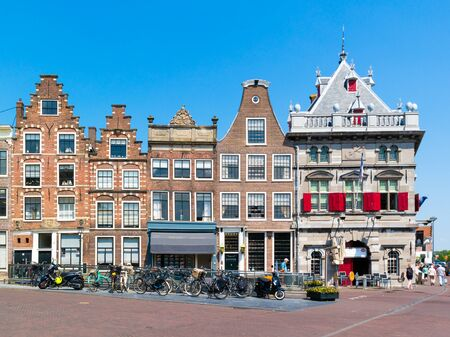 People walking, row of old houses and Waag on Damstraat in Haarlem, Holland, Netherlands Editorial