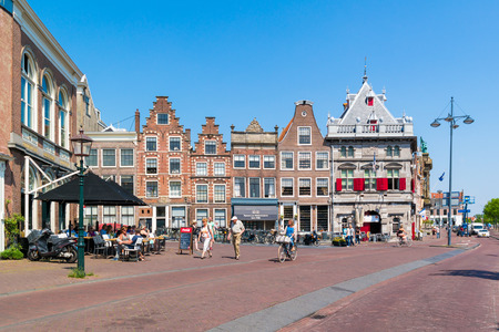 streetscene: People walking and cycling in Damstraat and Spaarne with facades of old houses and Waag in Haarlem, Holland, Netherlands