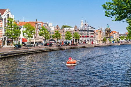 Spaarne river with row of old houses and weigh house in the city of Haarlem, Holland, Netherlands