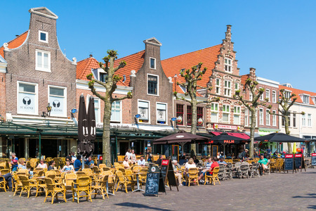 People enjoying vacation on outdoor sidewalk cafes on Botermarkt square in old town of Haarlem, Holland, Netherlands