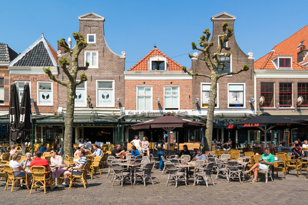 streetscene: People enjoying vacation on outdoor sidewalk cafes on Botermarkt square in old town of Haarlem, Holland, Netherlands