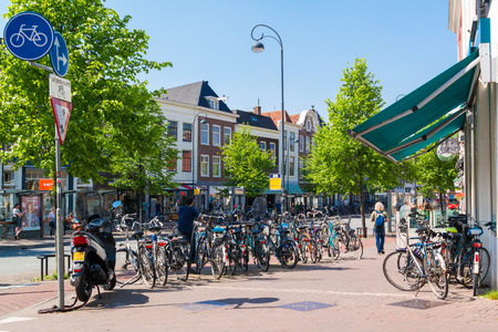 streetscene: Parked bicycles and people walking on Gedempte Oude Gracht street in downtown Haarlem, Netherlands