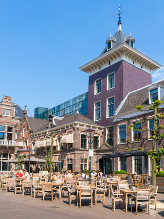 Outdoor cafe with people on Klokhuisplein square in city centre of Haarlem, Holland, Netherlands Editorial