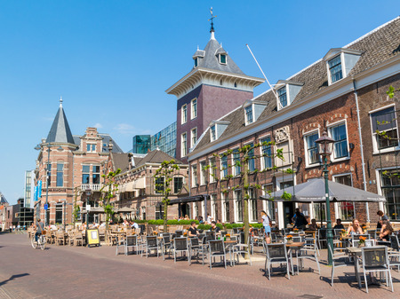 Klokhuisplein square with sidewalk cafe and people in old town of Haarlem, Holland, Netherlands Editorial