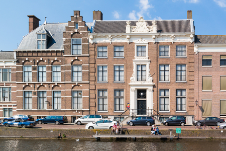 People at waterside in front of Episcopal Palace on Nieuwe Gracht canal in city centre of Haarlem, Netherlands