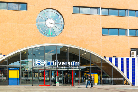 People walking in front of main entrance of railway station in Hilversum, Netherlands