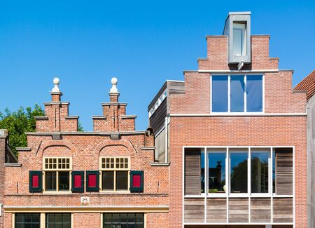 stepped: Top facades of stepped gables of old and modern brick house on Oudegracht in Alkmaar, Netherlands Editorial
