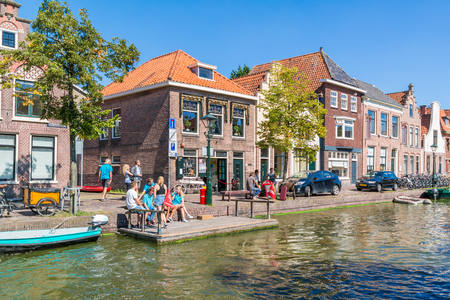 People on floating pontoon and houses on quayside of Verdronkenoord canal in Alkmaar, Netherlands