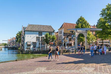 streetscene: People walking and sightseeing on quay near Bathbrug and Zijdam in Alkmaar, Netherlands