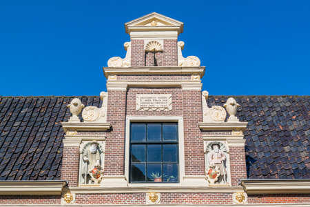 gable: Top gable with memorial stone and sculptures of Huis van Achten in Alkmaar, Netherlands Editorial