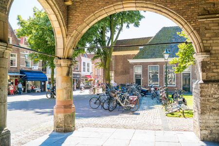 north holland: Bicycles and people shopping in Koorstraat from entrance arcades of Lawrence Church in Alkmaar, North Holland, Netherlands