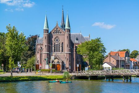 People in kayaks on Singelgracht canal and St. Joseph's Church in Alkmaar, Netherlands