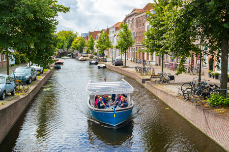 People enjoying sightseeing tour on boat on Rapenburg canal in old town of Leiden, South Holland, Netherlands Editorial