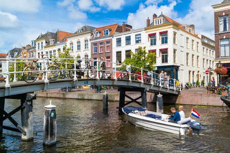 People and bicycles on bridge, boat on New Rhine canal and gables of historic houses in old town of Leiden, South Holland, Netherlands Editorial