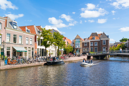 house gables: People in boat on Stille Rhine canal in old town of Leiden, South Holland, Netherlands