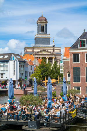 church tower: Hartebrugkerk church tower and people on outdoor terrace of cafe on Rhine canal in Leiden, South Holland, Netherlands Editorial