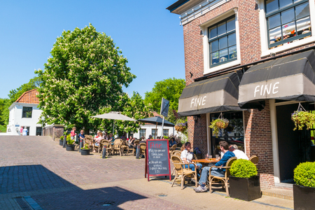 streetscene: People relaxing on outdoor terrace of cafe in old town of Naarden, North Holland, Netherlands Editorial