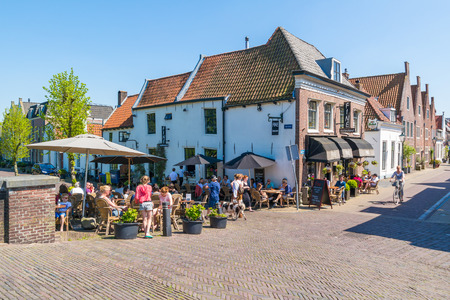 People relaxing on outdoor terrace of cafe on Oude Haven in old town of Naarden, North Holland, Netherlands 報道画像