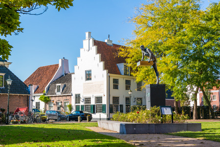 Street scene with donor memorial monument and house with stepped gable in old town of Naarden, North Holland, Netherlands