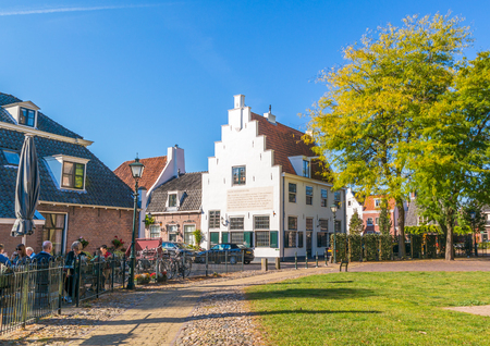 streetscene: Street scene with people on outdoor terrace and house with stepped gable in old town of Naarden, North Holland, Netherlands