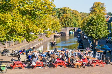 Mensen aan de waterkant terras van cafe en tourboat op kanaal in Naarden-Vesting, Noord-Holland, Nederland
