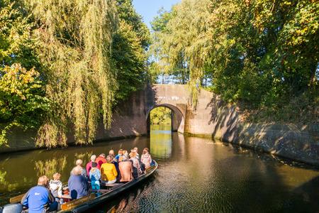 Mensen in de toeristenboot op kanaal in de herfst in de oude stad van Naarden, Noord-Holland, Nederland
