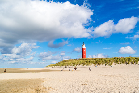 Beach with people and lighthouse of De Cocksdorp on island Texel, North Holland, Netherlands