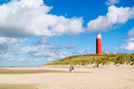 TEXEL, NETHERLANDS - SEP 18, 2016: Beach with people and lighthouse of De Cocksdorp on island Texel, North Holland, Netherlands