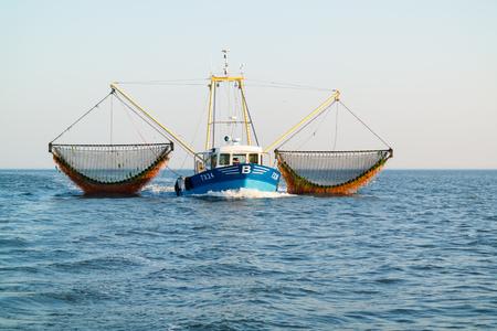 WADDENSEA, NETHERLANDS - SEP 13, 2016: Commercial outrigger trawler shrimp fishing on Waddensea, Netherlands