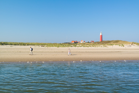 TEXEL, NETHERLANDS - SEP 14, 2016: Active pensioners walking on beach and De Cocksdorp lighthouse on West Frisian Waddensea island Texel, Netherlands