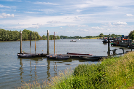 Jetty and boats on river Afgedamde Maas near fortified town of Woudrichem, Brabant, Netherlands