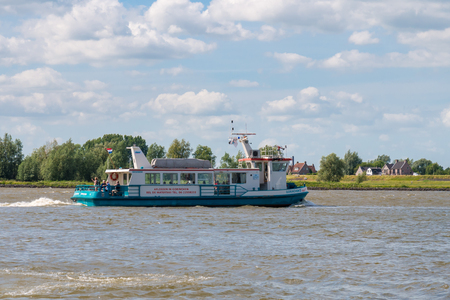 Ferry boat with people sailing on riverr Boven-Merwede from Woudrichem to Gorinchem, Netherlands