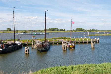 Aak op rivier Boven-Merwede en zeilboten in historische haven van oude vestingstad Woudrichem, Brabant, Nederland Stockfoto